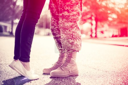 Young military couple kissing each other, homecoming concept, so