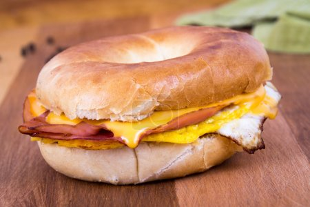 Photo for Ham, Egg and Cheese Breakfast Sandwich on a Bagel over a wood table - Royalty Free Image