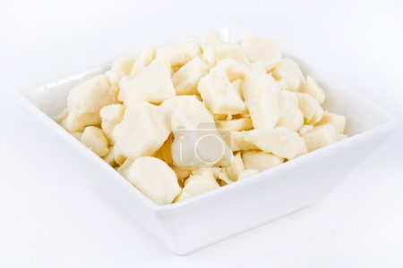 White dairy cheese curd in a bowl over white backg...