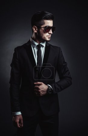 Photo for Portrait of handsome stylish man in elegant black suit and sunglasses - Royalty Free Image