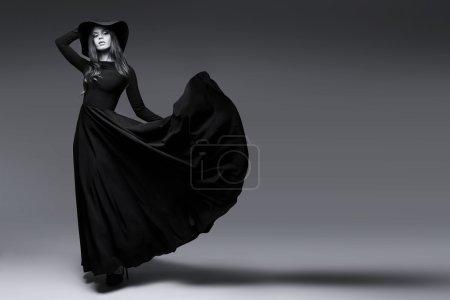 Photo pour Coup de haute couture de femme élégante dans un chapeau et robe longue flottante. Image en noir et blanc - image libre de droit