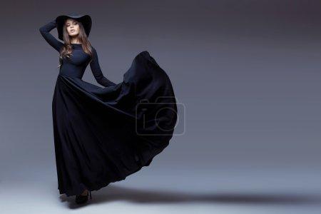Photo pour Plan de haute couture de femme élégante dans un chapeau et longue robe flottante . - image libre de droit