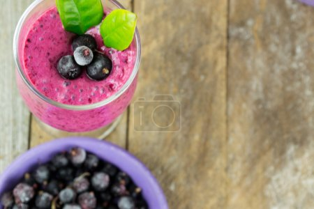 Milkshake with black currants in a glass against t...