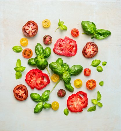 Photo for Various of sliced tomatoes with fresh basil leaves, top view - Royalty Free Image