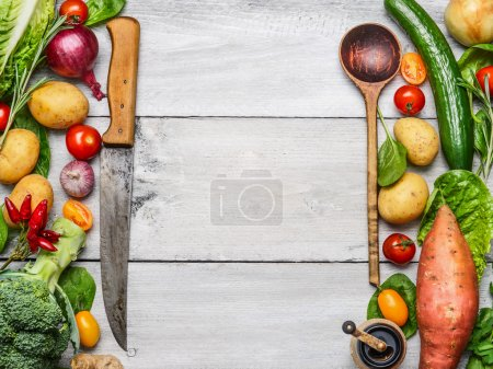 Photo for Delicious assortment of farm fresh vegetables with knife and spoon on white wooden background, top view. Vegetarian ingredients for cooking. Healthy cooking concept. - Royalty Free Image