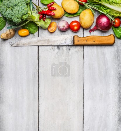 Photo for Fresh vegetable ingredients for cooking with used kitchen knife on white wooden background, top view. Vegan, diet or healthy cooking concept. - Royalty Free Image