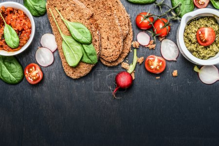 Photo for Ingredients and spread for vegetarian sandwich making on dark wooden background, top view, border - Royalty Free Image