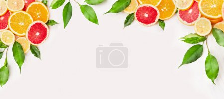 Photo for Citrus fruits slices with green leaves on white wooden background, banner for website - Royalty Free Image