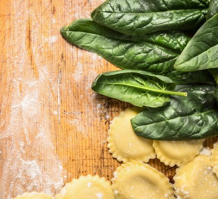 Tortellini with  fresh spinach leaves