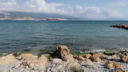 Photo for NOVOROSSIYSK, RUSSIA - CIRCA SEPTEMBER 2020: view on the Black Sea and big rocks on the shore in the port of Novorossiysk. - Royalty Free Image