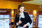 Krásná mladá dívka stojící v kanceláři a držení notebooku