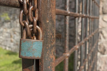 The lock on the chain. Old rusty chain with a lock on the iron gate. Symbol imprisonment and slavery. Property security chain. Closed iron gate with a lock.
