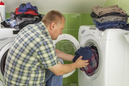 Man washes clothes in the washing machine. Housework men. Man helping his wife when washing clothes. The division of housework. Man Near The Washing Machine.