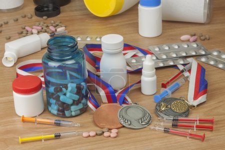 Doping in sport. Abuse of anabolic steroids for sports. Anabolic steroids spilled on a wooden table. Fraud in sports. Pharmaceutical industry. Detailed view of the medication. Place for your text.