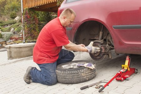 Man changing the punctured tyre on his car loosening the nuts with a wheel spanner before jacking up the vehicle. Repair flat tire on a passenger car. Replacing summer tires for winter tires.