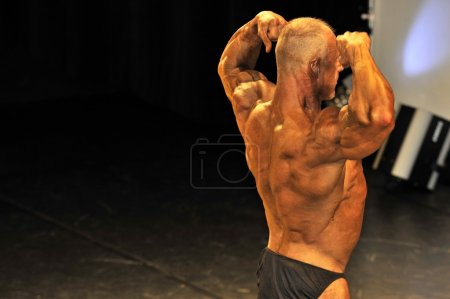 Male bodybuilding contestant showing his back double biceps pose