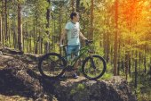 biker with bike on the rocks. Sport, adventure, motivation.