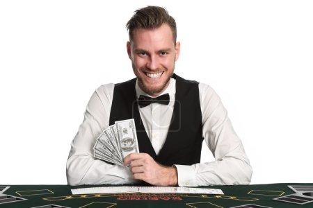 Photo pour Travailleur de casino mature porte un gilet noir et une chemise blanche avec un noeud papillon. Tenir un ventilateur de billets d'un dollar avec un jeu de cartes réparties en face de lui. Fond blanc. - image libre de droit