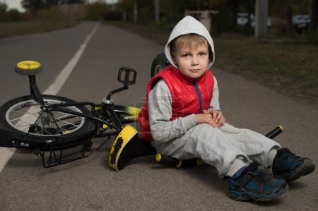 The boy fell off his bicycle