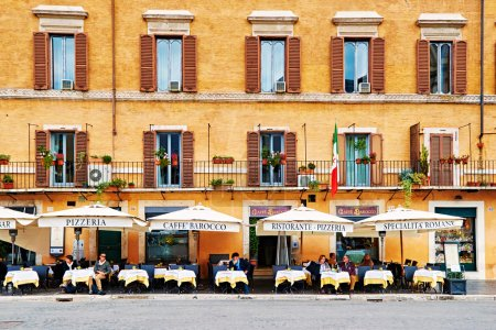 Guests sit on the beautifull restaurant terrace in Piazza Navona in Rome, Italy