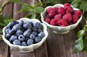 Raspberry with blueberry  in a bowls on a wooden table