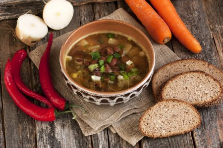 A healthy vegetarian bean soup in bowl on old wooden table