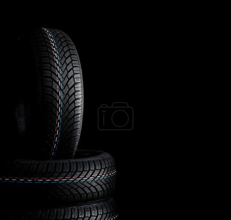 Photo for Car tires. Winter wheel profile structure on black background - Royalty Free Image