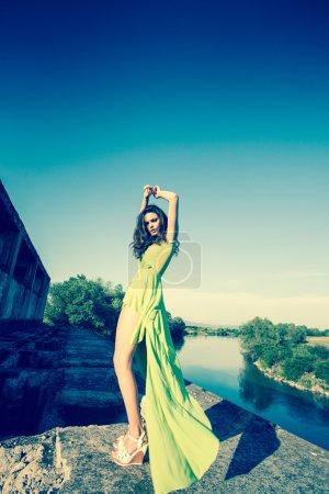 Photo pour Beau modèle en robe verte posant dans un endroit grunge - image libre de droit