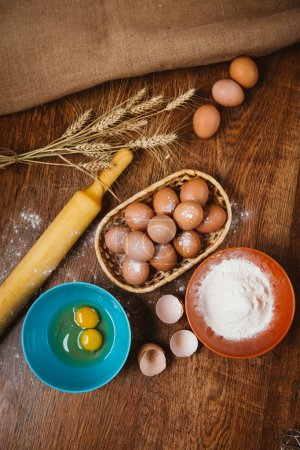 Baking cake in rural kitchen - dough  recipe ingredients eggs, flour, sugar on vintage  wooden table from above.