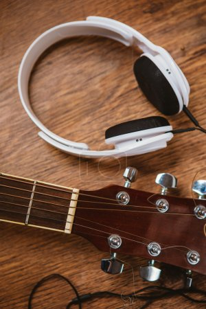 Photo for Acoustic guitar and headphone on  fabric sofa - Royalty Free Image