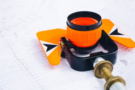 Orange theodolite prism lies on a background geodetic maps of the area