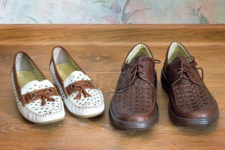 Photo pour À l'étage dans la maison sont près blanc womens mocassins et mens chaussures noirs en cuir. - image libre de droit
