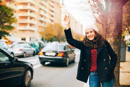 Photo pour Joyeux jeune belle femme appelant à un taxi avec bras levé dans la ville en automne - image libre de droit