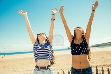Photo for Funny girl friends with arms outstretched greeting the sun on the beach - Royalty Free Image
