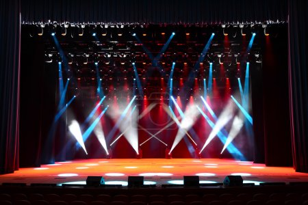 Photo for Illuminated empty concert stage with smoke and red, white and blue beams - Royalty Free Image