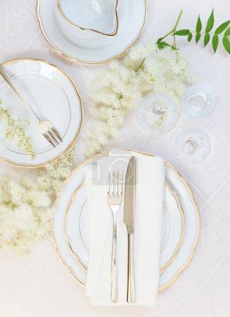 Photo pour Vue de dessus de la table joliment décorée avec des plaques blanches, verres en cristal, serviette lin, coutellerie et fleurs sur nappes luxueux - image libre de droit