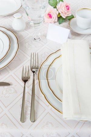 Photo pour Joliment décoré table avec plaques blanches, verres en cristal, couverts et fleurs sur les nappes luxueux, avec carte d'hôte - image libre de droit