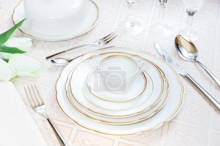 Photo pour Magnifiquement décoré de table avec des plaques blanches, verres en cristal, serviette lin, coutellerie et Tulipe fleurs sur nappes luxueux - image libre de droit
