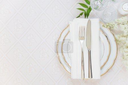 Photo pour Vue de dessus de la table joliment décorée avec des plaques blanches, verres en cristal, draps serviettes, couverts et fleur blanche sur des nappes luxueux, avec un espace pour le texte - image libre de droit