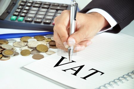 Hand with pen pointing to VAT (or Value Added Tax)...