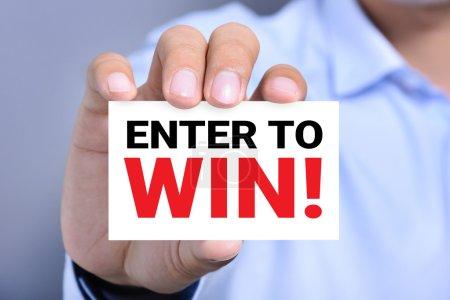 Photo pour Entrez pour gagner!, message sur la carte qui s'est tenue par une main d'homme - image libre de droit
