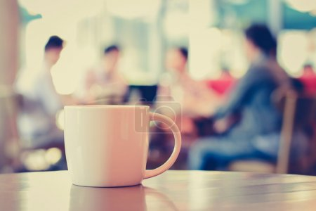 Coffee cup on the table with people in coffee shop...