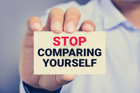 STOP COMPARING YOURSELF, message on the card shown by a man