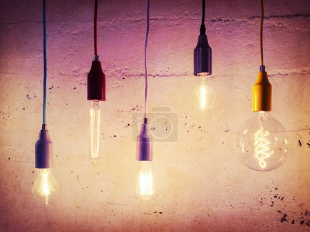 Photo for Illuminated light bulbs on concrete wall background. Industrial design. - Royalty Free Image