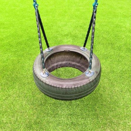 Foto de Columpio de neumático sobre fondo de hierba verde. Juegos de niños. - Imagen libre de derechos