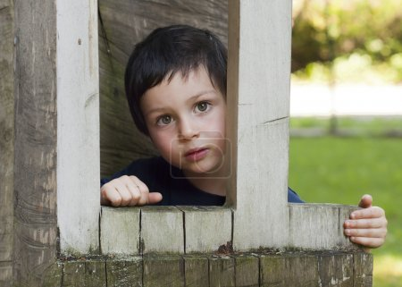 Child in wooden window in playhouse