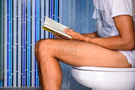 Photo pour Gros plan de l'homme lisant un livre tout en déféquant dans les toilettes privées . - image libre de droit