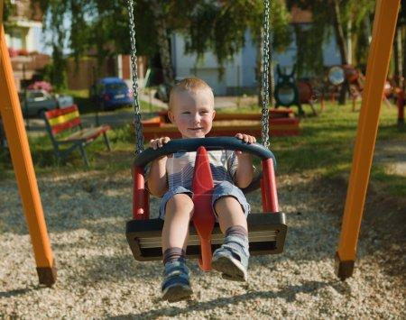 Photo pour Petit garçon se balancer sur une balançoire dans le parc - image libre de droit