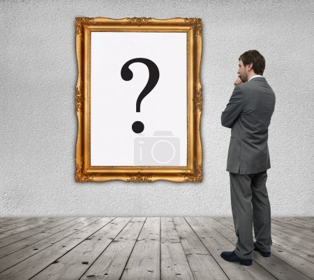 Photo for Young Businessman watching the question mark in a gold frame - Royalty Free Image