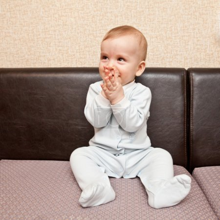 Child in a blue suit sitting on a sofa